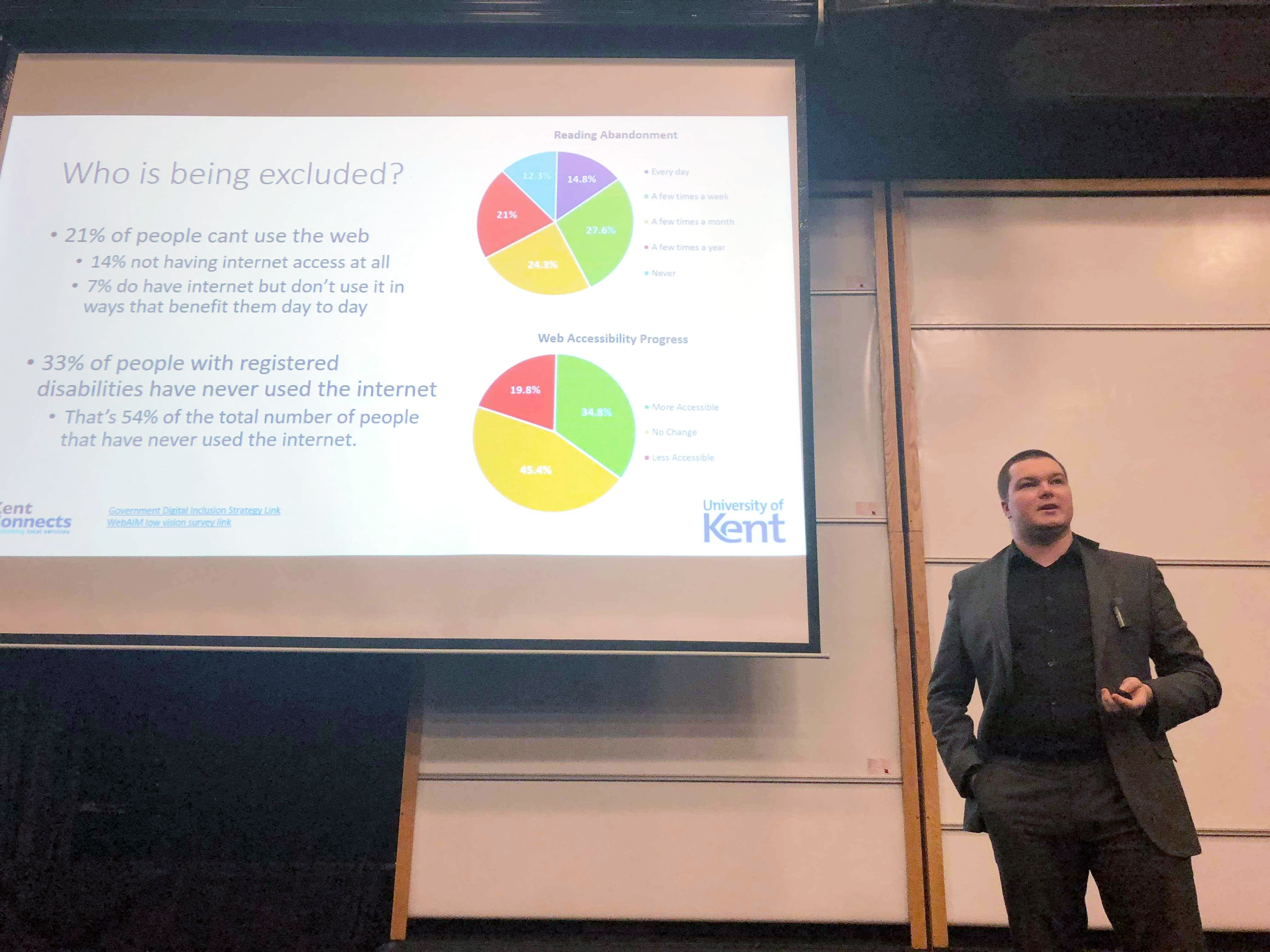 An image of George Rhodes, KCC Digital Accessibility Compliance Lead, giving a lecture at the University of Kent on Accessibility and its importance for students is the services they build. The picture shows George standing next to his slides, which are displaying figures on the levels of digital exclusion in the UK. The slides shown are available to download elsewhere on this page.